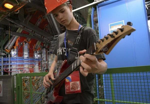 Джона Кон играет на гитаре в ЦЕРНе на фоне коллайдера