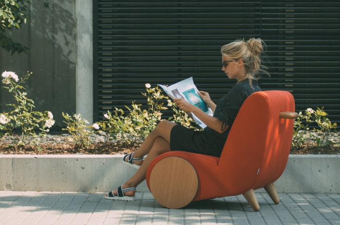 Дизайн уютного мягкого кресла на деревянных колесах.