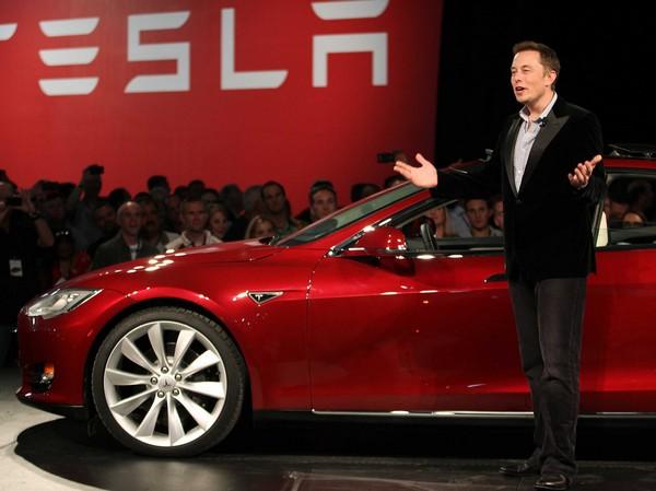 Илон Маск на фоне электромобиля Tesla